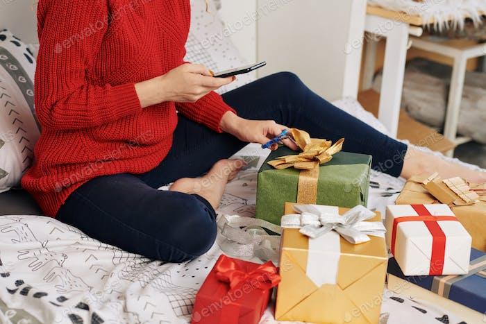 Frau postiert Foto von verpackten Geschenken