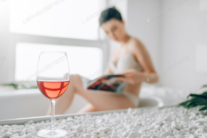 Glass of red wine, woman in bath on background