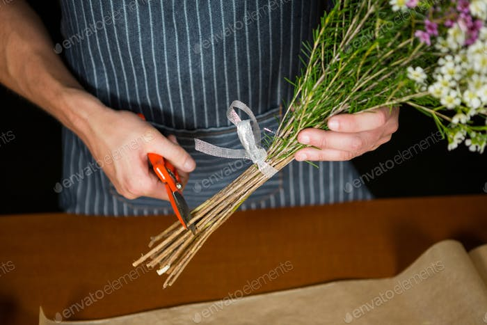 Male florist trimming flower stem in flower shop