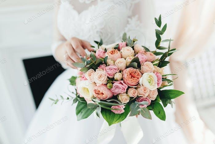 Bride in white dress is holding wedding bouquet