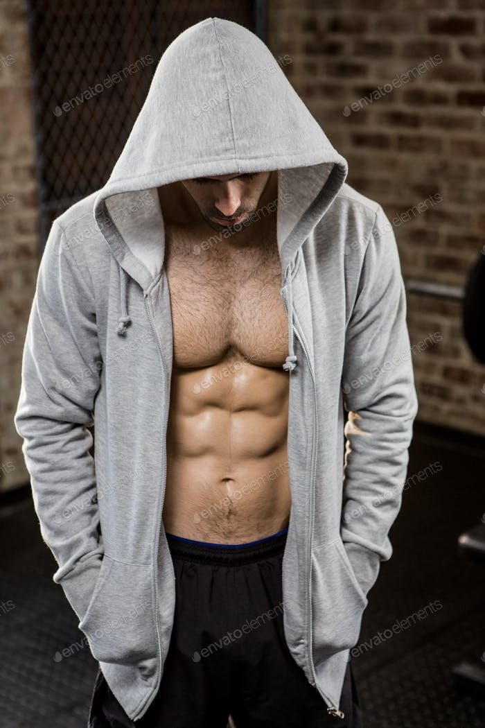 Muscular man wearing hood at the gym