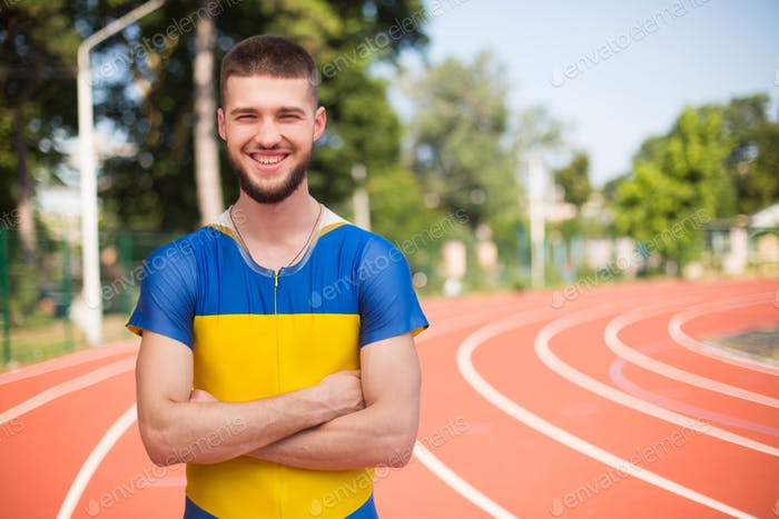 Young professional sportsman happily looking in camera while spending time on treadmill of stadium