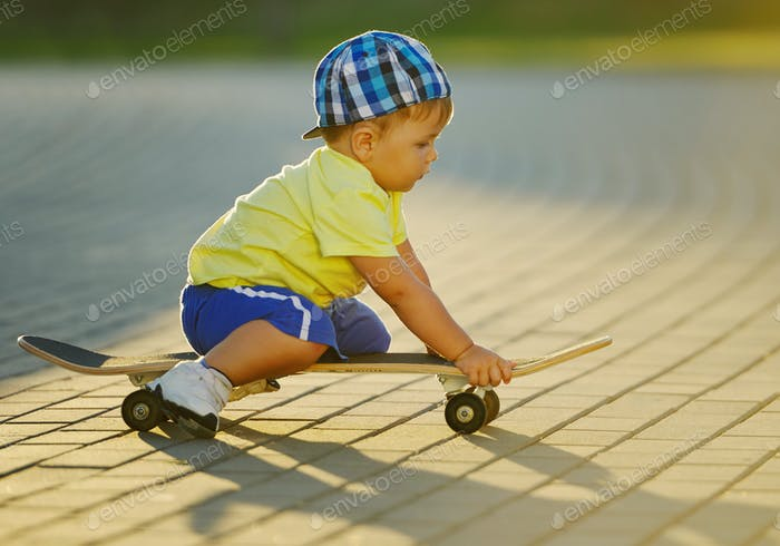 cute little boy with skateboard outdoors