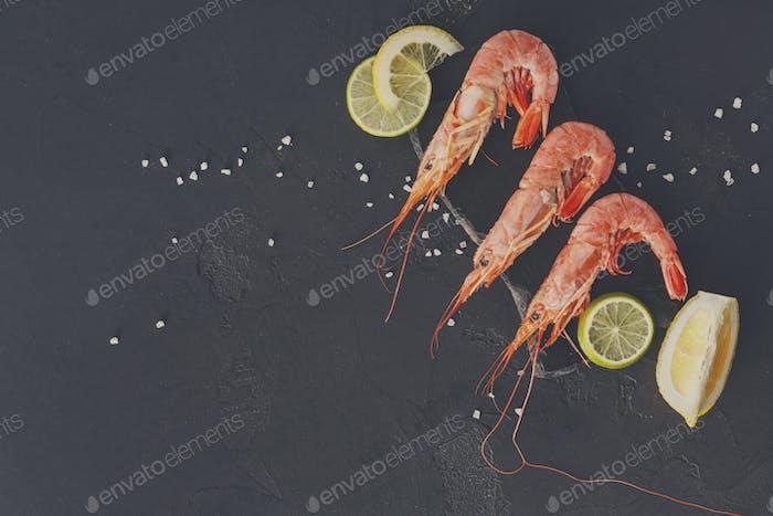 Shrimps with salt and lemon on black background