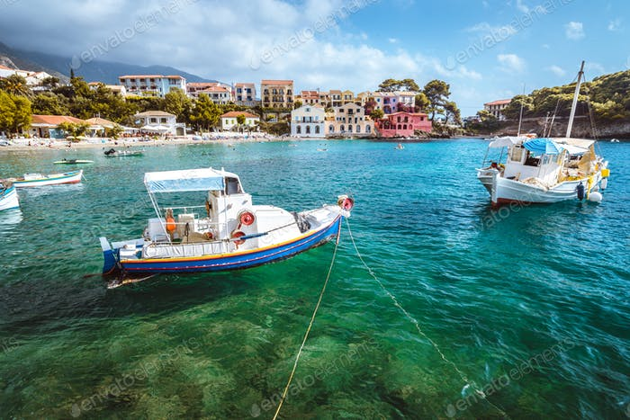 Assos village on Kefalonia island, Greece. White blue local boats at anchor in the emerald rippled
