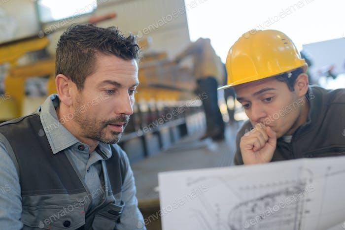männlicher Vorgesetzter mit Arbeiter diskutiert über Blaupausen in der Industrie