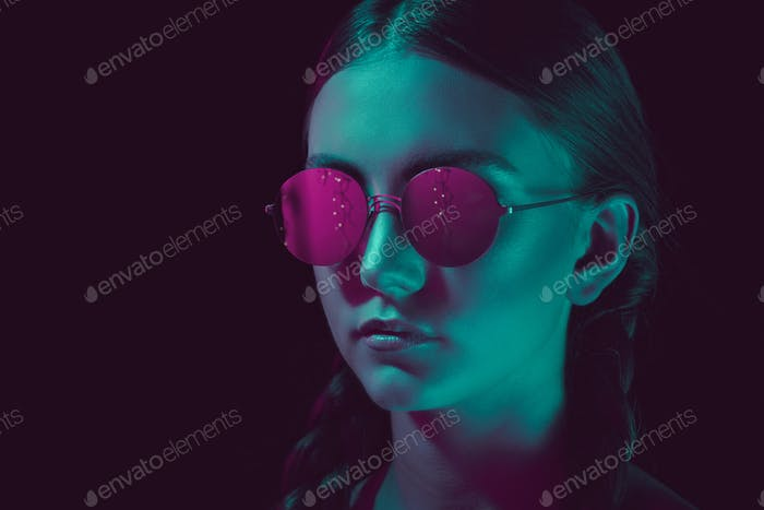 headshot of thoughtful young woman in stylish round sunglasses