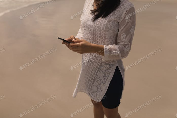Mid section of young woman using mobile phone on beach in the sunshine
