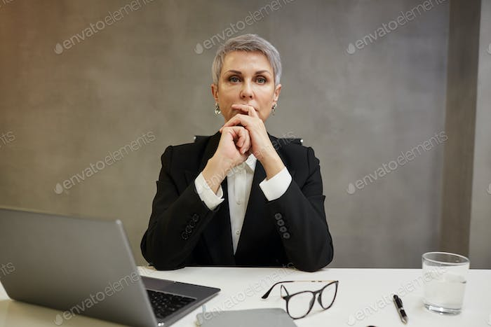 Pensive Mature Businesswoman at Desk