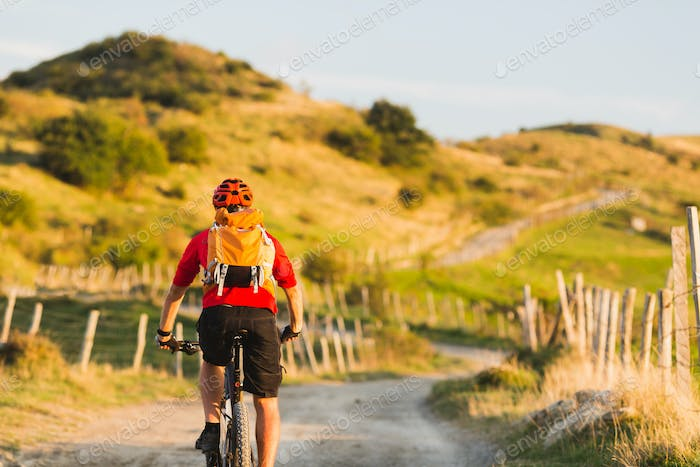 Bicycle riding enduro adventure in sunset mountains