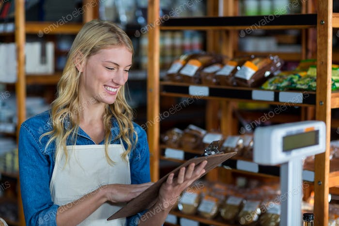 Smiling female staff looking at clipboard