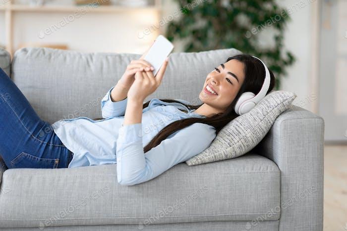 Entspanntes Wochenende. Happy Korean Girl In Wireless Kopfhörer Musik hören Auf Smartphone