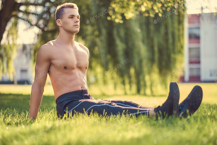 Концепция здорового образа жизни. Безрубашки молодой человек отдыхает, сидя на зеленой траве.