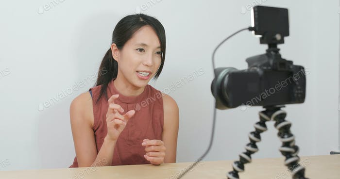 Woman talking in front of the camera to make vlog