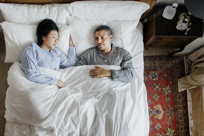 Interracial couple sleeping together on the bed
