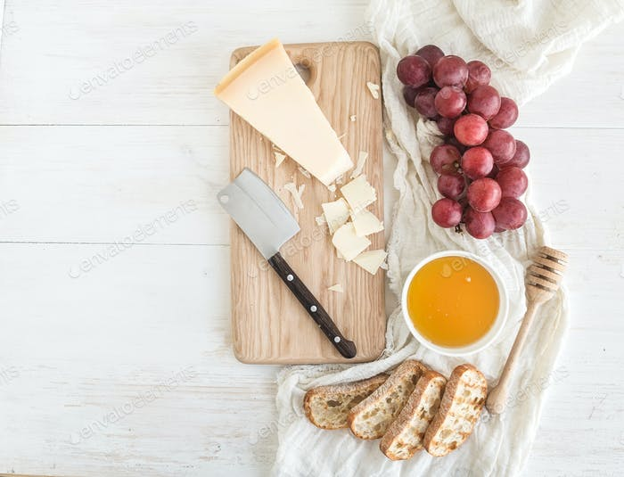 Parmesan cheese with grapes, honey and bread slices on wooden chopping board