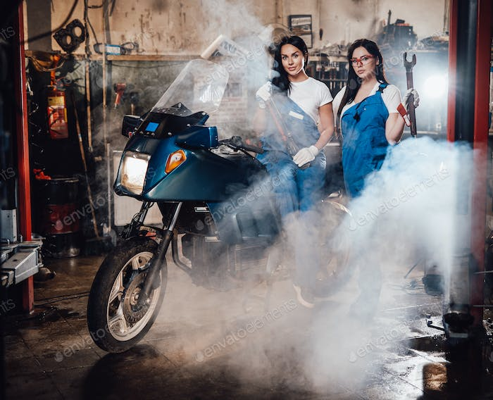 Two female mechanic posing next to a sportbike in authentic workshop garage surrounded by smoke