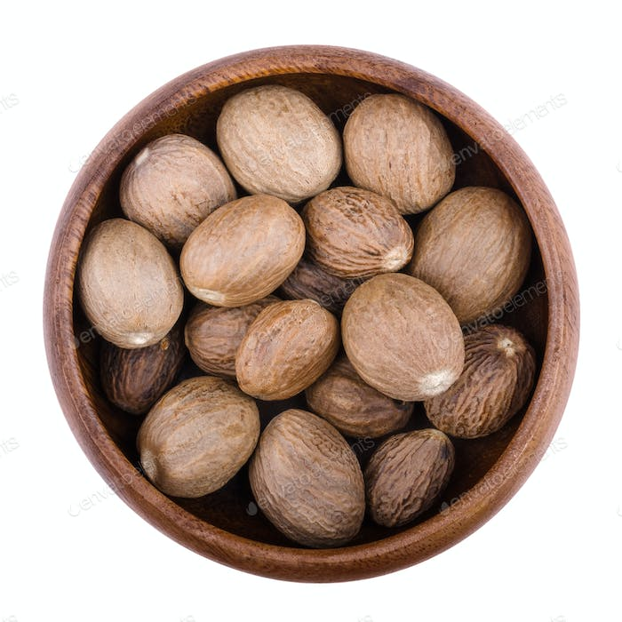 Nutmegs in a bowl over white