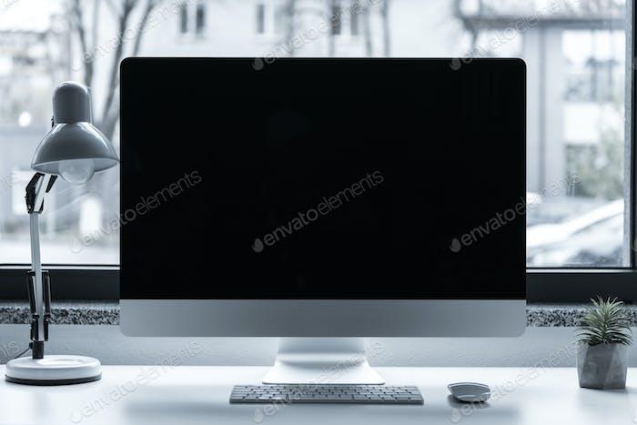 Arbeitstisch mit Computer vor dem Fenster
