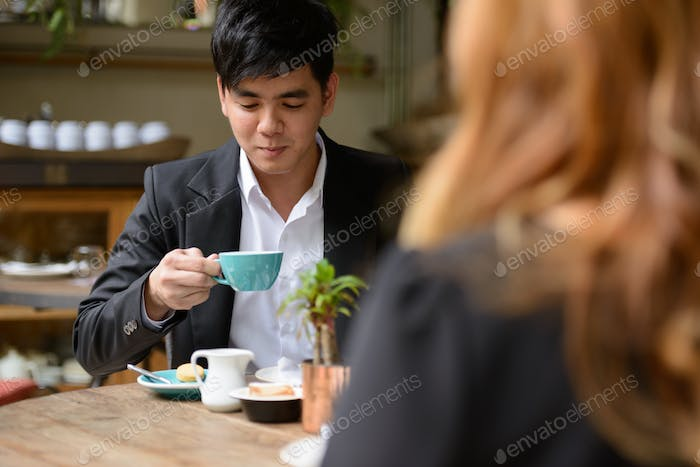Young Asian business couple drinking coffee together at the coffee shop