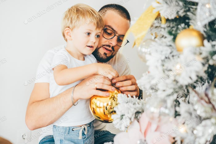 Young father with son decorate the Christmas tree.