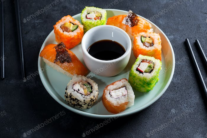 Various Fresh and delicious sushi set on ceramic plate with slate sticks, sauce and nori on black