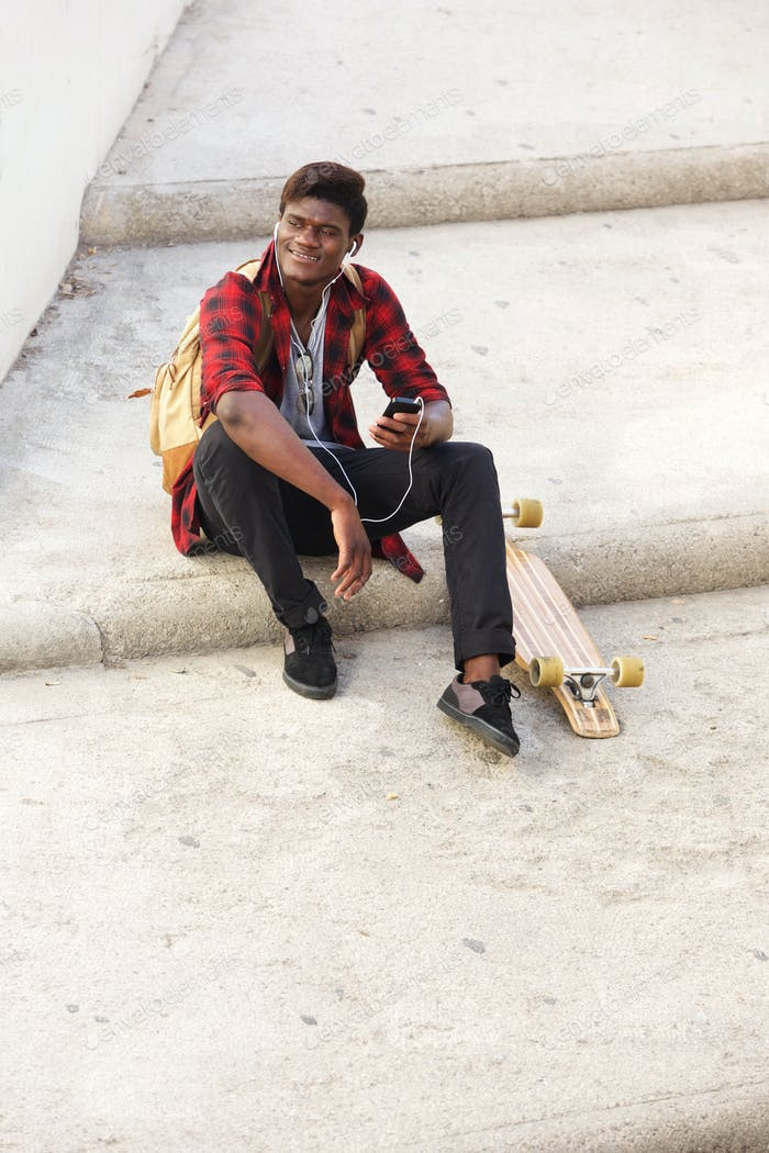 happy african american guy sitting outside on steps with mobile phone and skateboard
