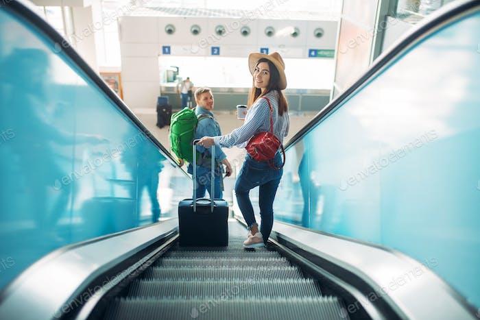 Paar mit Gepäck klettern die Rolltreppe, Flughafen