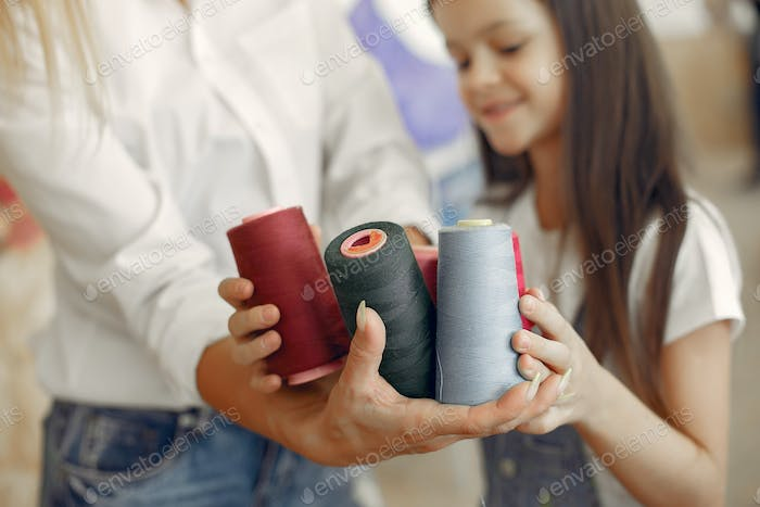 Mother with little daughter standing at the fabric with thread