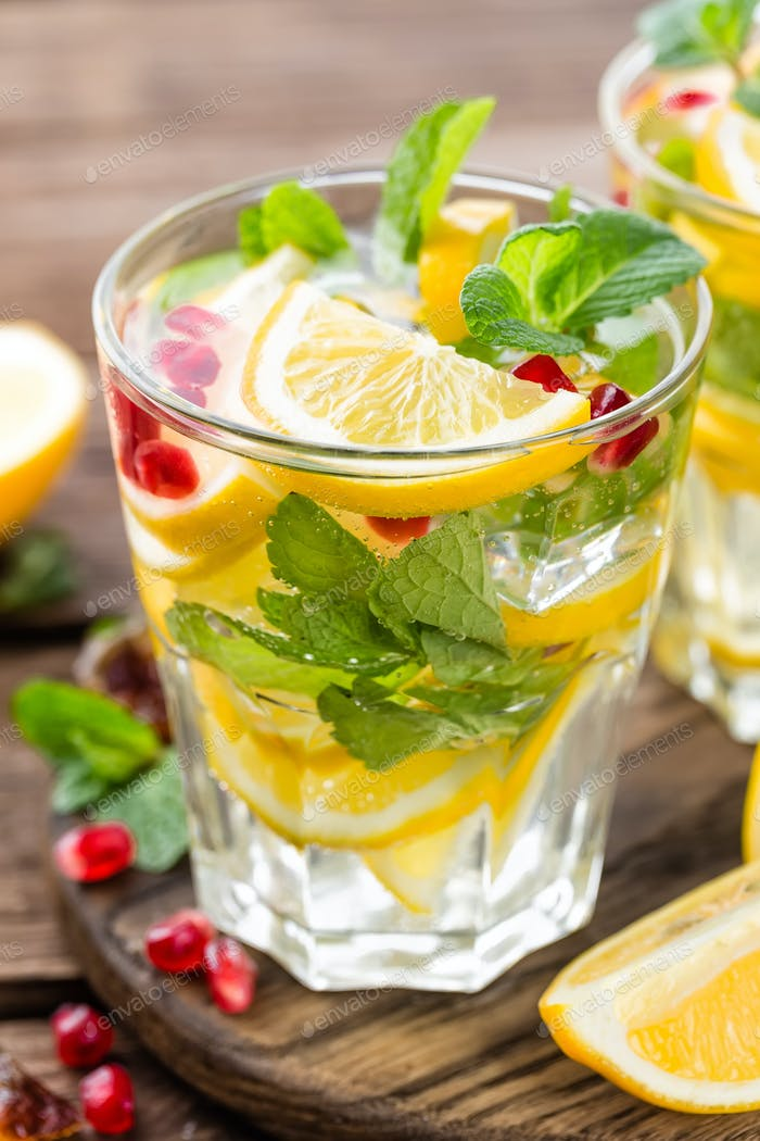 Lemon mojito cocktail with mint and pomegranate, cold refreshing drink or beverage