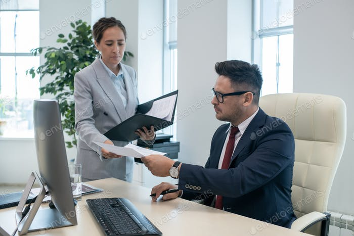 Boss passing signed document to his secretary