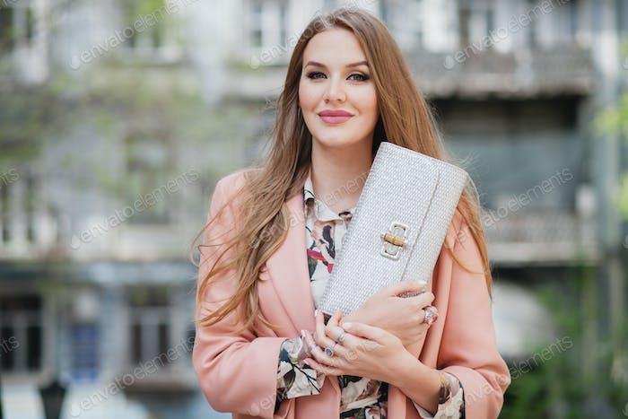 cute young beautiful stylish woman walking in street in pink coat