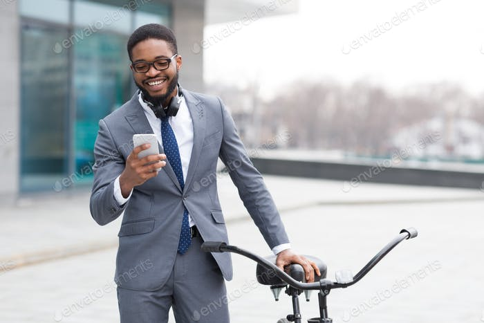 Happy entrepreneur texting on phone near bicycle