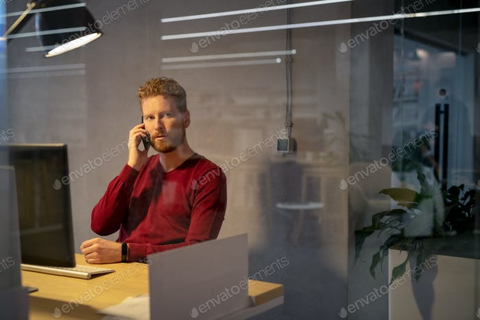 Worried business man talking on phone late in office