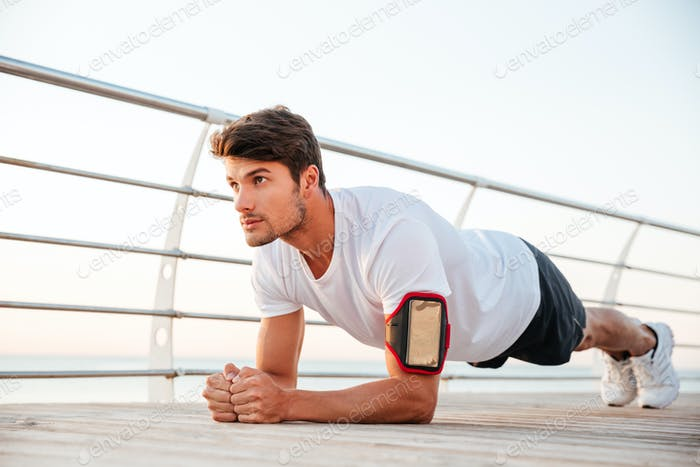 Handsome young serious sportsman doing plank exercise at the pier