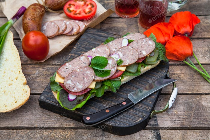 Sandwich with sausage slices, tomato and lettuce, top view