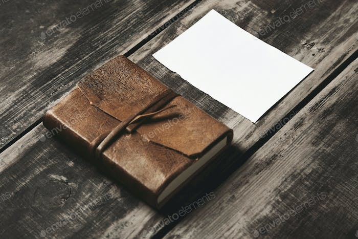 notebook in leather cover and paper sheet on black table