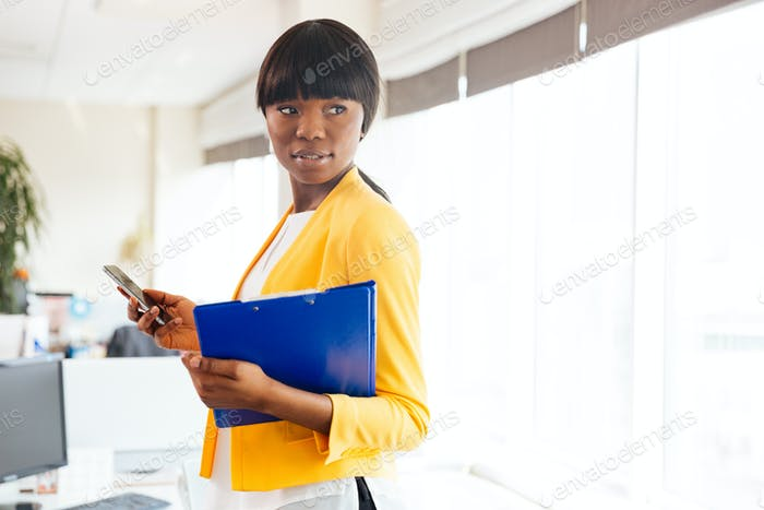 Afro american businesswoman holding folder and smartphone