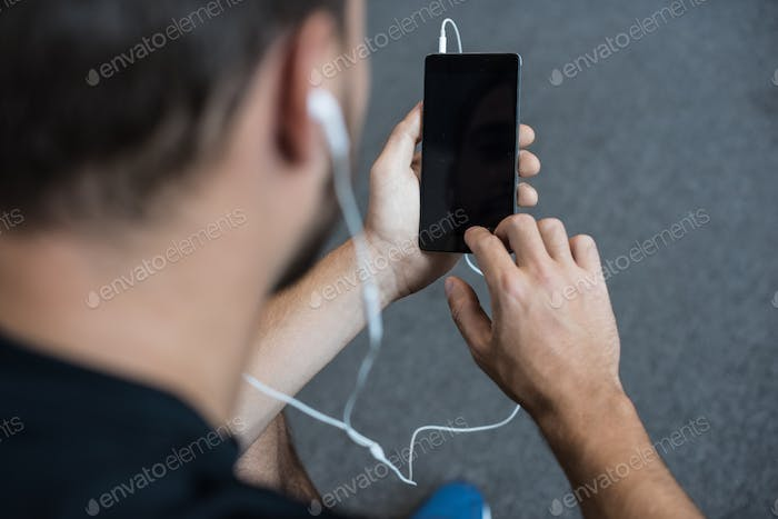 Cropped shot of young man in earbuds using his smartphone