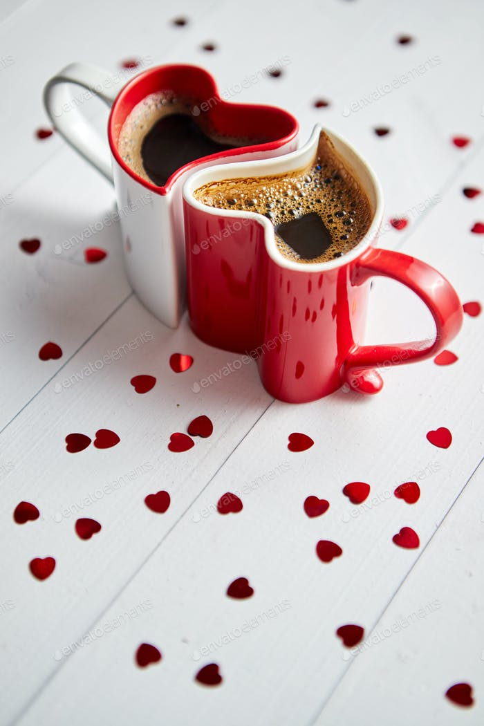 Two heart shaped coffee cups conected with each other