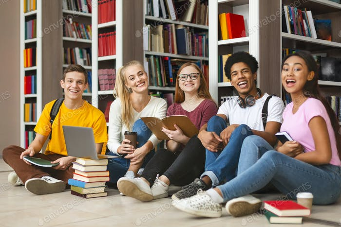 Group of diverse teenage classmates sitting on library floor