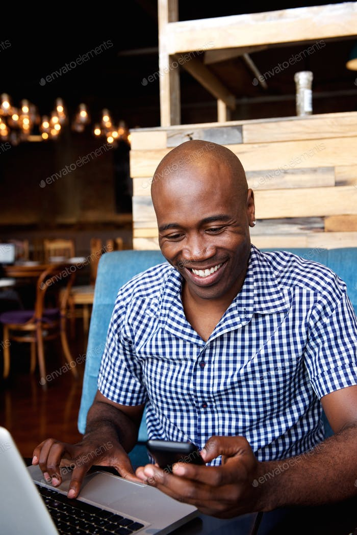 Smiling man looking at mobile phone