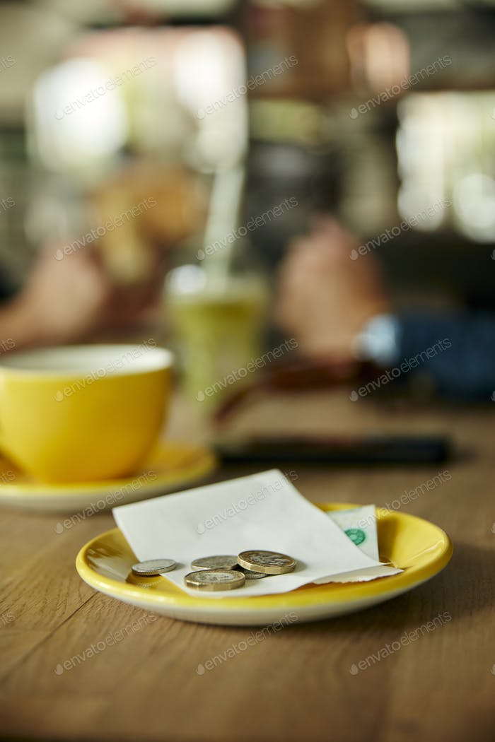 Coins and bill on cafe table