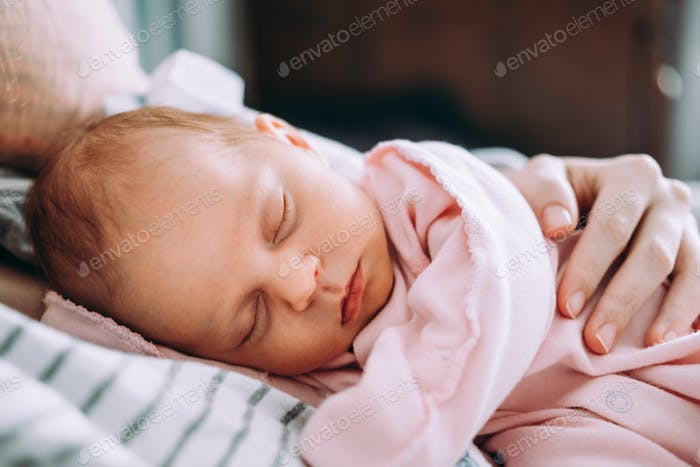 Cute newborn baby sleeping with mother. Happy Family concept.
