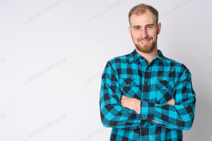 Portrait of happy young bearded hipster man smiling with arms crossed
