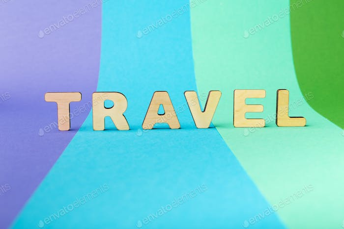 Travel word inscripted with wooden letters on colorful background