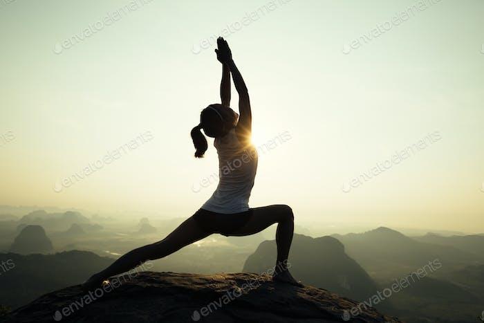Yoga woman on sunrise mountain top