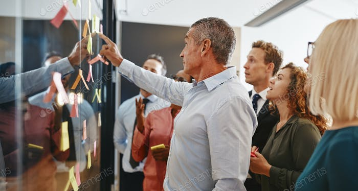 Diverse businesspeople brainstorming together with sticky notes in an office