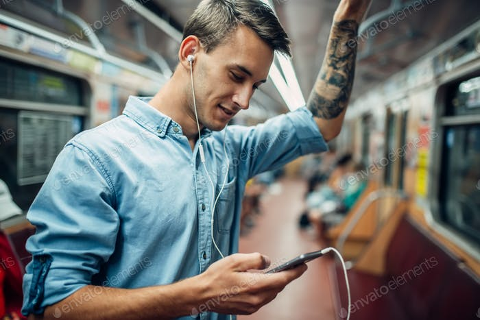 Young man using phone in metro, addicted people