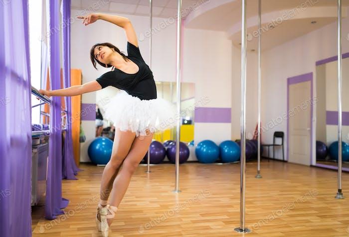 Woman making ballet class near ballet machine in dance studio